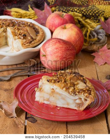 Slice of fresh apple pie with walnut topping on a wooden surface