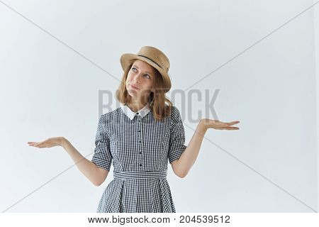 Horizontal shot of pretty woman in romantic dress and headwear posing in studio looking away with questioning puzzled facial expression feeling confused about choosing something or making decision