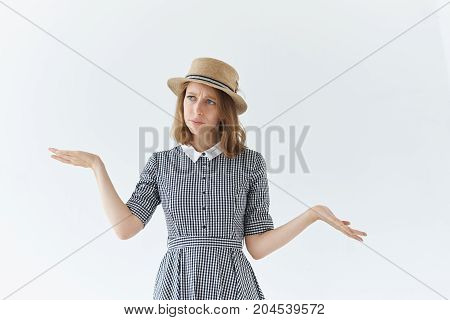 Genuine human emotions reaction and feelings. Studio picture of indecisive doubtful young lady shrugging shoulders and gesturing in indifference saying: Who knows Whatever It doesn't matter