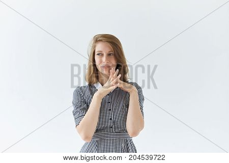 Mysterious charming young lady wearing collar dress clasping hands looking with sly thoughtful expression. Portrait of cute girl having idea smiling mysteriously standing at white blank studio wall