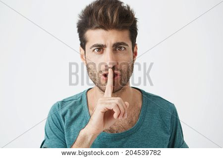 Headshot of attractive stylish caucasian male in casual blue t-shirt, holding index finger at lips, asking to keep silence in library