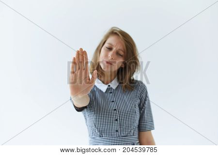 Studio shot of inaccessible beautiful young woman making stop gesture with hand refusing to give her nubmer to some guy. Pretty female expressing denial refusal and prohibition with stop sign