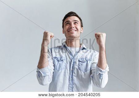 Joy victory celebration triump and excitement concept. Picture of euphoric ecstatic student celebrating his success and education achievement clenching fists feeling happy and excited saying Yes