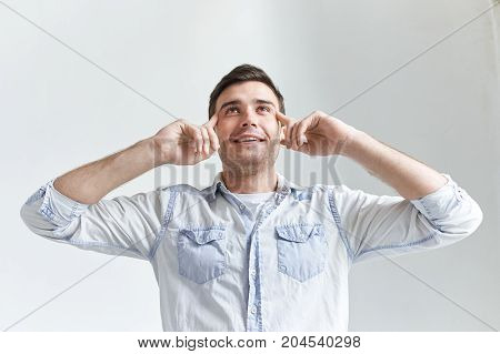 Let me think. Isolated portrait of positive handsome young male with stubble looking up and holding fingers on his temples trying to remember thing or word that he has at the tip of his tongue