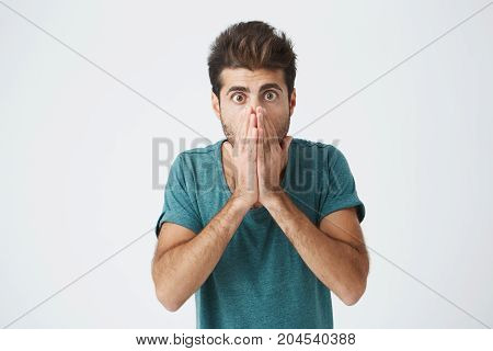 Attractive unshaven young hispanical man in blue tshirt, covering his face with hand looking in full disbelief after received bad news