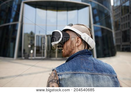 Modern lifestyle futuristic technology innovation and cyberspace concept. Back view of stylish bearded guy in denim vest testing oculus 3d glasses with head mounted display walking in urban setting