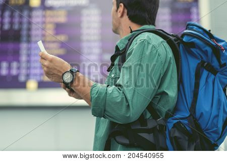 Time to go. Low angle of cute adult guy with tickets in his hands and backpack is waiting for flight in modern airport terminal while standing in front of electronic information board. Side view
