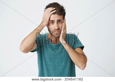 Close up portrait of mature caucasian bearded man in blue t-shirt, holding hand on forehead and cheek looking tired and bored after long day at work