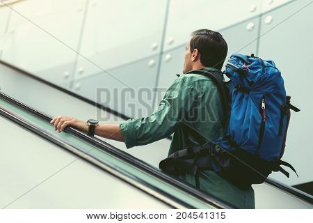 Always on move. Low angle of cute traveler with backpack is climbing-up on escalator at modern airport. Back view