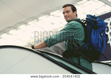 Enjoying trip. Cheerful young guy with backpack is standing on moving staircase at modern airport while looking at camera with joy