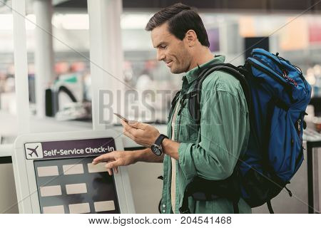 Customer service. Profile of positive man with backpack is looking at his smartphone and using self-service check-in monitor at international airport building