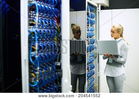 Portrait of young woman working with supercomputer standing in server room holding laptop, copy space