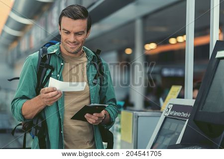 Ready for cute journey. Delightful man with backpack is standing nearby self-service check-in kiosk and looking at his boarding pass with smile. Copy space in the right side