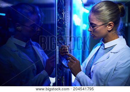 Side view portrait of beautiful young woman wearing lab coat connecting wires in server cabinet while working with supercomputer in blue light