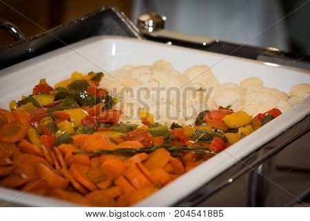 Food banquet table with vegetables in chafing dish heater on a festive event - selective focus on food