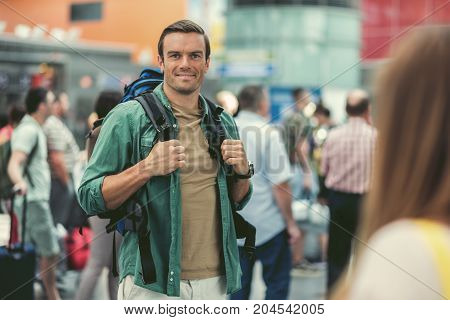 Feeling happy. Portrait of stylish young guy is standing in international airport with hand luggage and looking at camera with joy. Passengers on background. Focus on man