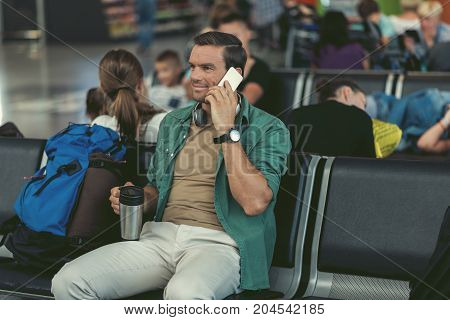 Good news. Positive adult guy is talking on smartphone while drinking coffee in waiting room of international airport with passengers on background