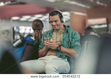 Choosing song. Selective focus of joyful young guy is holding mobile phone and listening to music through headphones with smile while sitting in waiting room of international airport