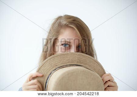Portrait of cute strange mysterious young female model with enigmatic blue eyes covering face with round retro hat. Beautiful girl posing at white wall peeking out from beige straw headwear