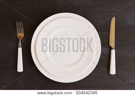 Tableware - set of plates and utencils on dark wooden background