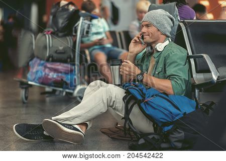 Talk with friends. Stylish adult guy is having pleasant conversation on mobile phone. He is drinking beverage while sitting on floor of international airport and expressing gladness