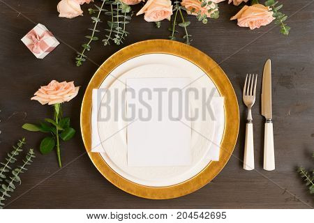 Tableware - set of plates and utencils with flowers on wooden background