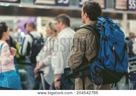 Adult man with backpack is standing in line at international airport with passengers on background. Back view. Copy space in the left side