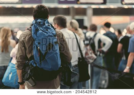 Selective focus of guy with backpack is standing in line at modern airport. Back view. Copy space in the right side