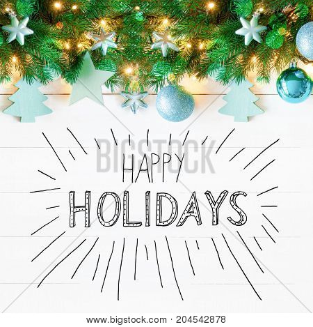 Christmas Garland With Turquoise Christmas Ball Ornament. Fir Brances With Fairy Lights. White Wooden Background With English Calligraphy Happy Holidays