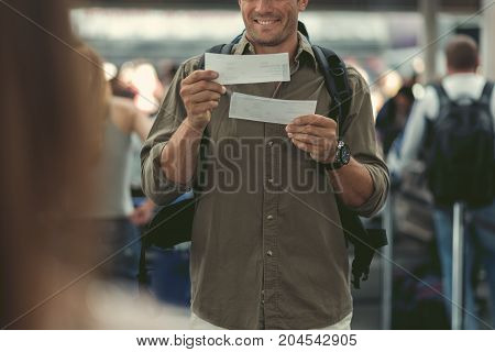 Lets travel. Cheerful cute adult man with backpack is standing at international airport and holding tickets while expressing gladness. People on background