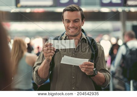 Extremely happy. Delightful young cute guy with backpack is looking at his boarding pass and expressing gladness while waiting for his flight