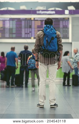 Where is my plane. Full-length of young traveler with backpack is standing in international airport and looking at electronic information board. Back view. Passengers on background.