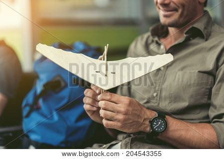 Eco toy. Close-up of wooden model of hang glider in hands of cheerful man who is sitting at modern airport with smile