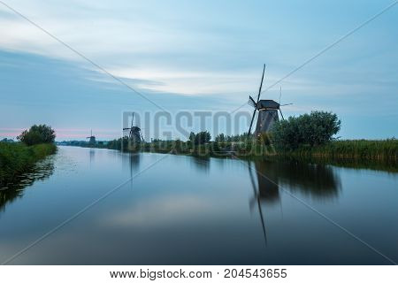 Windmills are lined up in evening light at the waterside at Kinderdijk.