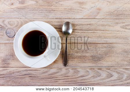 White Cup with coffee on a platter and spoon on wooden background