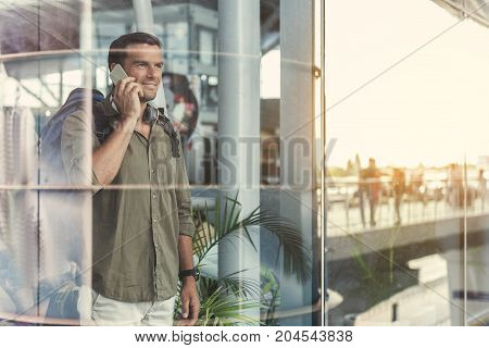 Pleasant call. Happy young man with backpack is talking on mobile phone while expressing gladness. He is looking out through window glass while standing in airport lounge. Copy space in right side
