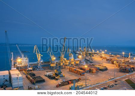 ALBANIA DURRES - September 22 2015: View of the cargo terminal in the evening. Unloading of the tanker by cargo cranes. A platform for storing sea freight containers. Cruise liners and cargo ships are moored in the port