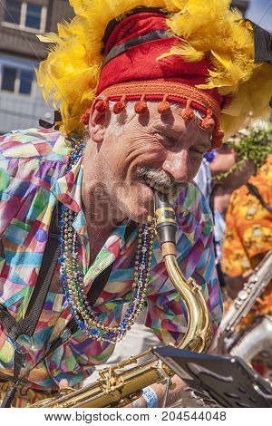 SEATTLE, USA - JUNE 22 2013: An unidentified musician with a feathered cap plays the saxophone as part of Honkfest in the Fremont Summer Solstice Parade in Seattle.