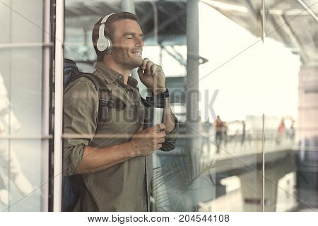 Joyful young man is enjoying music through headphones while drinking coffee. He is standing with closed eyes at airport lounge and expressing pleasure. View from glass window. Copy space