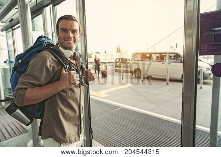 Finally at home. Happy young man with backpack and headphones is exiting from international airport. He is looking at camera with joy. Copy space in the right side
