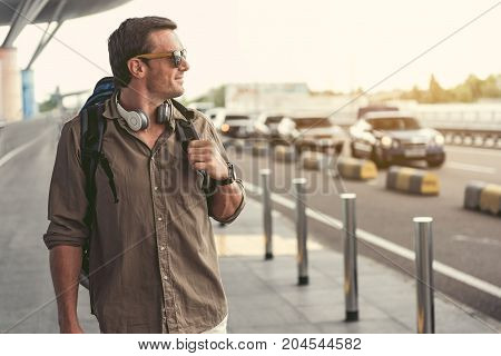 I am at home. Positive stylish adult man with headphones is standing near airport on street. He is holding backpack and looking aside with aspiration and smiling. Copy space in the right side