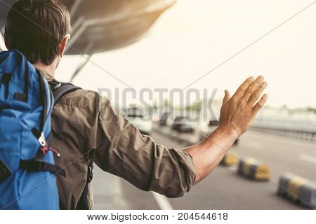 Back view of tourist with backpack is standing near road and raising hand. He is trying to catch car. Copy space on the right side