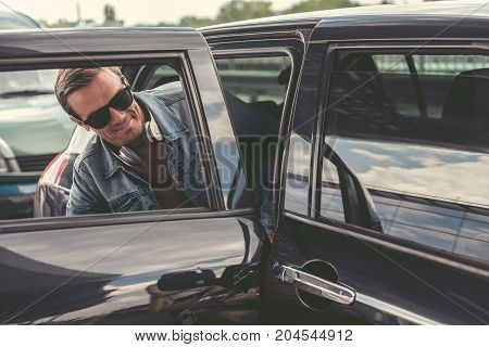 Pleasant man in sunglasses is sitting on the back seat of black automobile. He is expressing gladness. Copy space on the right side
