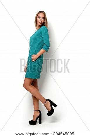 Young happy beautiful full body brunette woman posing in new fashion green dress cloth on a white background
