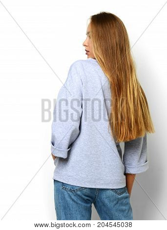 Young happy beautiful woman posing in new fashion blue jeans and gray pullover backside rear view on a white background
