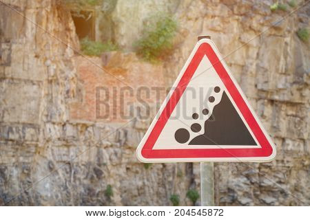 Road sign Caution rockfall against the background of a rock