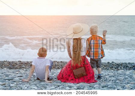 Mom And Two Sons Sitting On The Beach And Watching The Waves. View From The Back