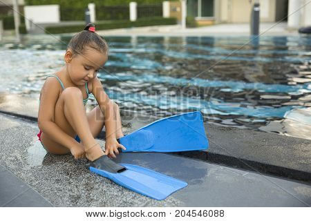 cute girl with flippers in swimming pool at tropical beach