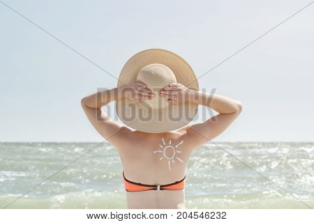 Girl With Hands Behind Head, Painted Sun On Back. Sea In The Background
