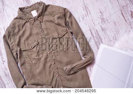 Khaki-colored Shirt With Rivets, Blank Sheet. Wooden Background, Space For Text. Fashion Concept